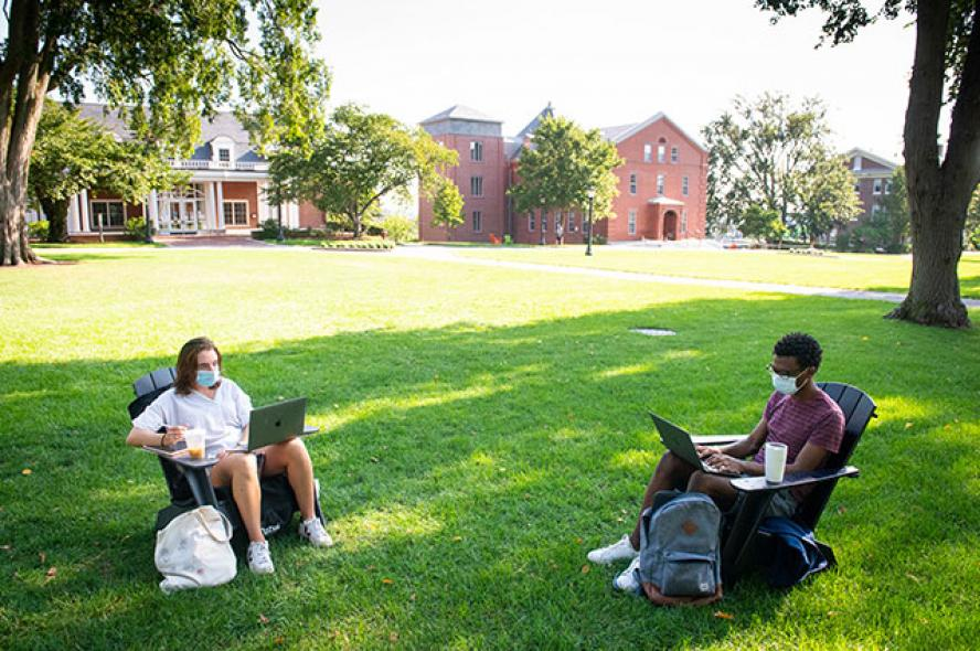 Students sit on Adirondack chairs on Academic Quad while they attend class on the first day of the fall semester