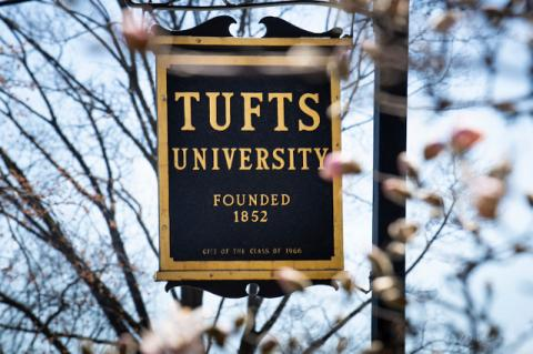Tufts University sign beside a flowering tree. Tufts emergency response grants are offered to community nonprofits in Medford, Somerville, Boston, and Grafton.