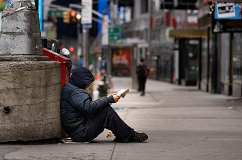 A homeless man sits on a New York City street made nearly empty by COVID-19. Tufts University School of Medicine alumni who care for the underserved talk about what they are learning from the pandemic.