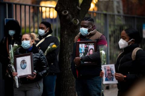 A group of Black health-care workers in New York march while carrying photos of colleagues who died of COVID-19. The health disparities faced by people of color in the pandemic are shown in stark relief by the pandemic, Tufts experts say