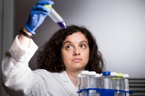 Marta Gaglia, an assistant professor at Tufts School of Medicine, looks at a test tube. She studies the way viruses infiltrate cells without tripping the immune system's alarms.