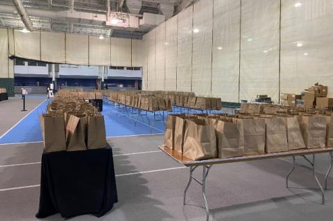 Rows of paper bags on tables in a gymnasium. Tufts organized meals for students staying on campus over Thanksgiving, with help from local restaurants