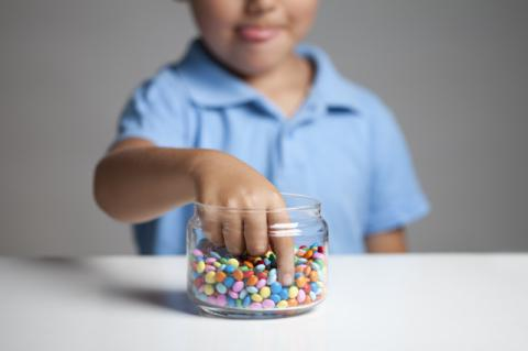 A young child reaching their hand into a jar of candy. It's likely that many children have put on the pounds during COVID-19, with potential long-term consequences, says a Tufts nutrition expert